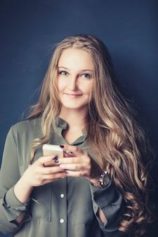 スマートフォンで灰色の背景に若い感情的な女性のクローズアップの肖像画