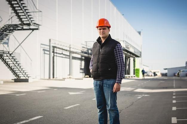 倉庫でポーズをとってヘルメットをかぶった若いエンジニアの肖像画