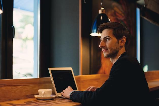 Портрет молодого предпринимателя работает на ноутбуке