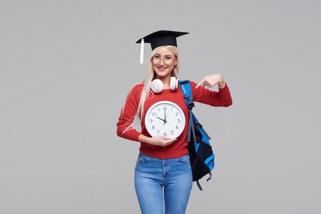 灰色の空間に分離された大きな目覚まし時計を保持しているバックパックと大学院のキャップで若い興奮した金髪の女性学生の肖像画。大学での教育。テキストのスペースをコピー