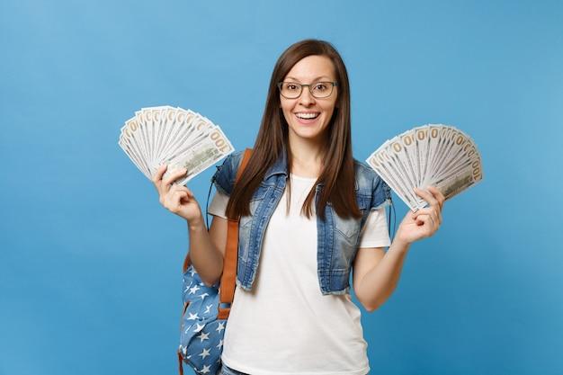 たくさんのドル、青い背景で隔離の現金を保持しているバックパックとメガネで若い興奮した楽しい女性学生の肖像画。高校大学カレッジコンセプトの教育。