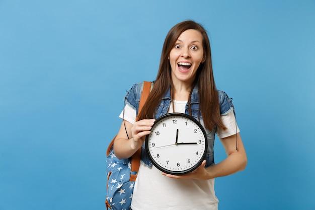 Портрет молодого взволнованного студента красивой женщины в джинсовой одежде с рюкзаком, держащим будильник, изолированный на синем фоне. время уходит. обучение в колледже. скопируйте место для рекламы.