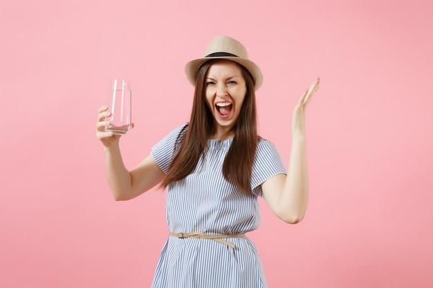 파란 드레스를 입은 젊은 흥분한 여성의 초상화, 모자를 들고 분홍색 배경에 격리된 유리에서 맑고 깨끗한 물을 마시고 있습니다. 건강한 생활 방식, 사람, 진실한 감정 개념. 공간을 복사합니다.
