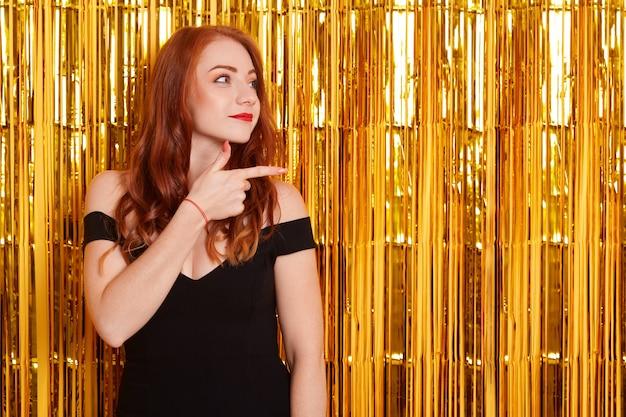 옆으로 손가락으로 가리키는 우아한 드레스에 젊은 흥분된 여자의 초상화, 황금 반짝이로 장식 된 벽 위에 절연 포즈