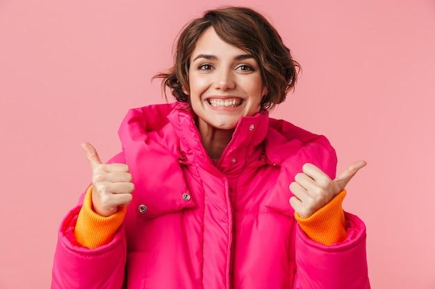 親指を立てて、ピンクで隔離の笑顔で暖かいコートを着た若い興奮した女性の肖像画