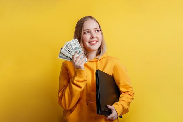 돈 달러 지폐와 노트북의 스택을 들고 젊은 흥미로운 웃는 예쁜 여자의 초상화. 돈, 온라인 수입, 복권 당첨을 꿈꾸는 10대 소녀는 노란색 배경에 격리되어 있습니다.