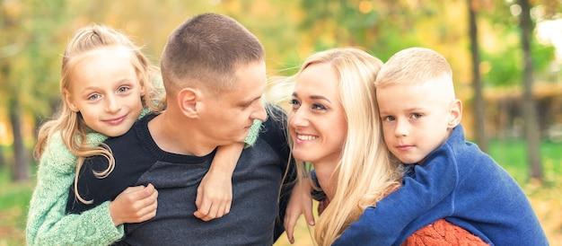 秋の公園で若い家族の肖像画