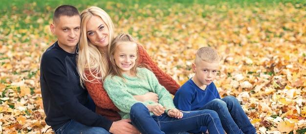 紅葉に座っている若い家族の肖像画