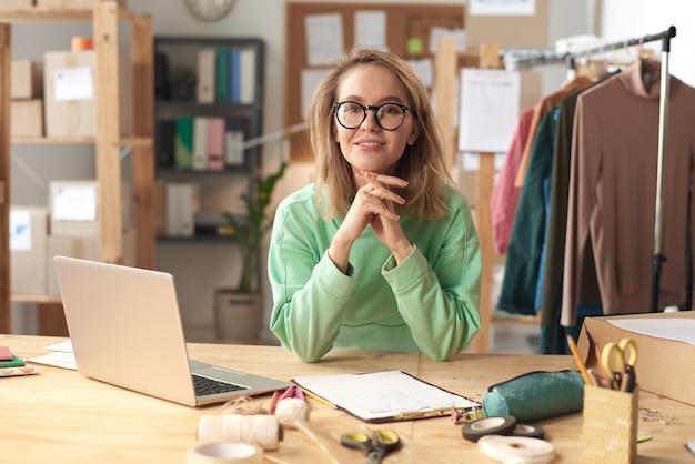 Портрет молодого модельера в очках, улыбаясь вперед, сидя за столом перед ноутбуком