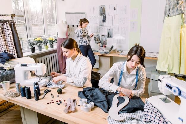 Портрет молодой модницы портнихи за работой. портниха, портной, мода и концепция шоу-рума - портрет талантливых портних, работающих с текстилем для пошива одежды