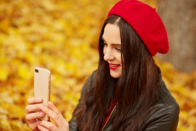 Портрет молодой модной девушки с смартфон в руках, глядя на devive, сидя на земле в парке осенью. модная женщина одевает красный берет и куртку в парк, принимая селфи для социальной сети