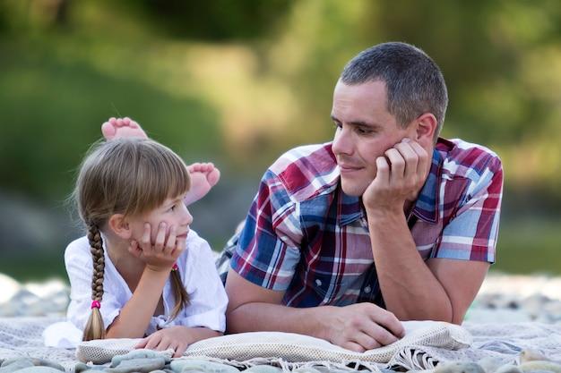 Портрет молодого отца и милой белокурой девушки при длинные оплетки кладя на pebbled речной берег на яркий летний день на запачканной зеленой предпосылке bokeh деревьев.