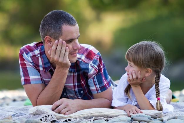 Портрет молодого отца и милая белокурая девушка при длинные оплетки кладя на pebbled речной берег на яркий летний день на запачканном зеленом bokeh деревьев. любви, заботы и прекрасного отдыха.