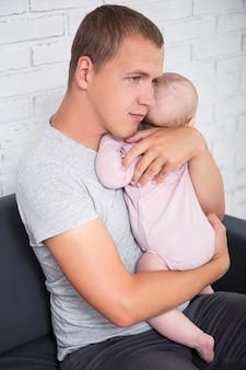 집에서 여자 아기를 안고 있는 젊은 아버지의 초상