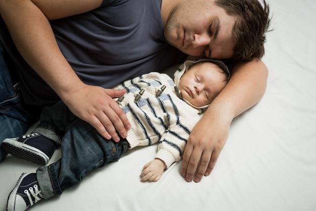 生まれたばかりの赤ちゃんの男の子と一緒にベッドで寝ている若い父親の肖像画