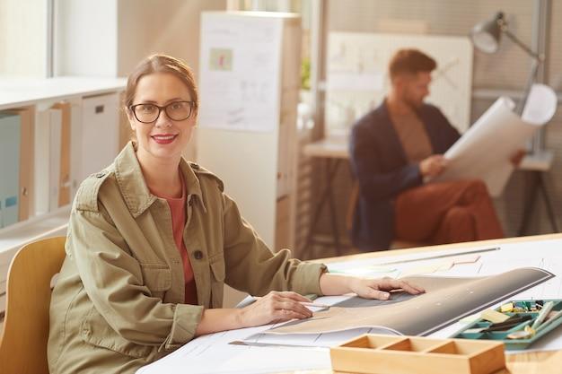 Портрет молодой женщины-архитектора, глядя в камеру и улыбаясь, сидя за столом для рисования в солнечном свете,