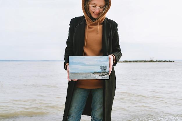 Портрет молодой художницы, стоящей на пляже и держащей картину маслом на берегу моря