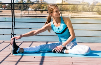 Portrait of young female athlete stretching her leg sitting at outdoors