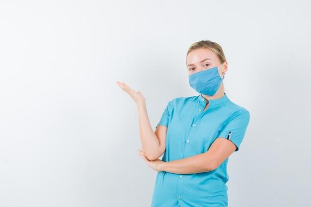 孤立した制服で何かを保持している若い女性医師の肖像画
