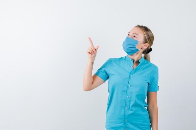 젊은 여성 의사 유니폼을 가리키는 사려 깊은 찾고의 초상화