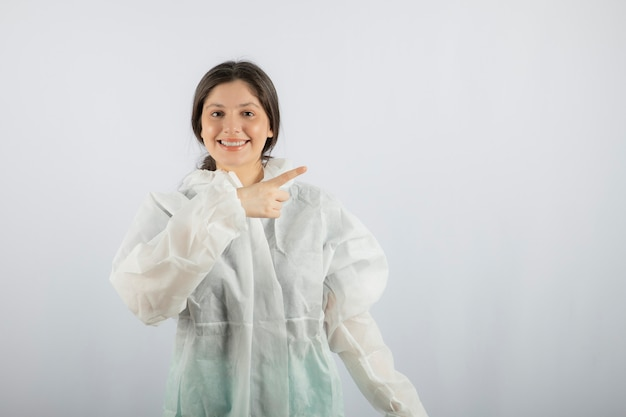 멀리 가리키는 방어 실험실 코트에 젊은 여성 의사 과학자의 초상화.