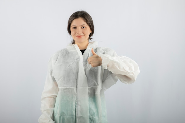 엄지손가락을 보여주는 방어 실험실 코트에 젊은 여성 의사 과학자의 초상화.