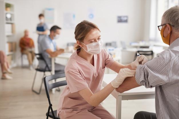 예방 접종 센터나 의료 클리닉에서 노인에게 예방 접종을 하는 젊은 여성 의사의 초상화, 복사 공간