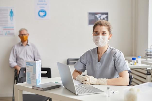 클리닉이나 예방 접종 센터에서 환자를 기다리는 동안 마스크를 쓰고 카메라를 보는 젊은 여성 의사의 초상화, 복사 공간