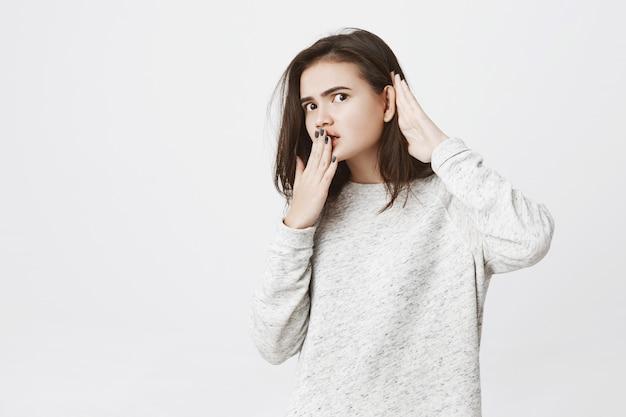 Портрет молодой работницы подслушивая или подслушивая что-то, держась за руки возле рта и ушей.