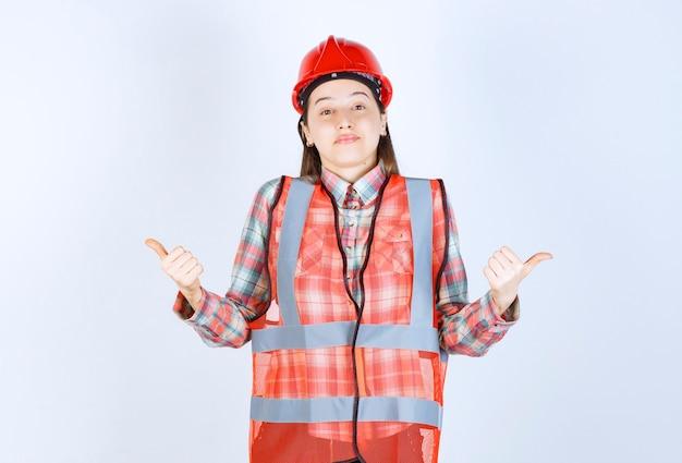 親指をあきらめるヘルメットの若い女性エンジニアの肖像画。