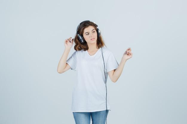 白いtシャツ、ジーンズ、夢のような正面図でヘッドフォンで音楽を楽しんでいる若い女性の肖像画
