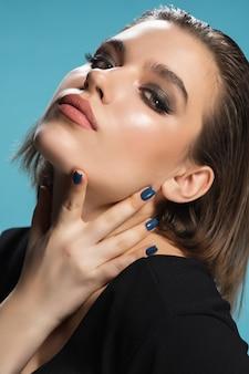 파란색 배경에 고립 된 젊은 여성 패션 모델의 초상화.