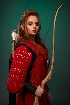 Портрет молодой женщины-истребителя в красной броне, держащей доу и смотрящей в камеру в студии
