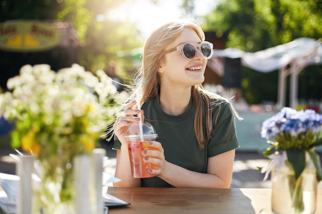 Портрет молодой женский пищевой блоггер, пьющий лимонад в очках и улыбаясь.