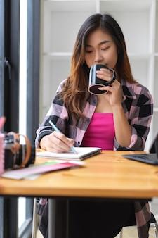 カフェで空白のノートに書いている間コーヒー休憩を飲む若い女性のフリーランサーの肖像画