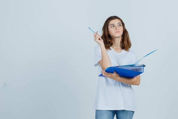 흰색 티셔츠, 청바지에 폴더와 펜을 들고 잠겨있는 전면보기를 찾고 젊은 여성의 초상화