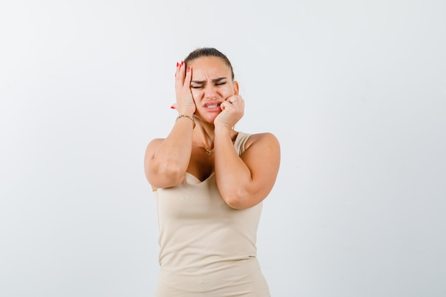 Портрет молодой женщины, держащей руки за щеки в бежевой майке и выглядящей недовольным видом спереди