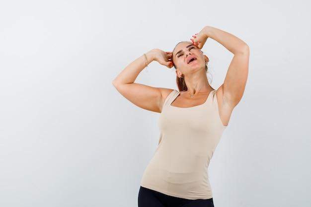 Портрет молодой женщины, держащей руки за голову в бежевой майке и выглядящей расслабленным видом спереди