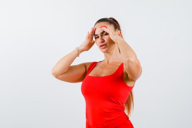Портрет молодой женщины, держащей руки за голову в красной майке, брюках и выглядящей измученной, вид спереди