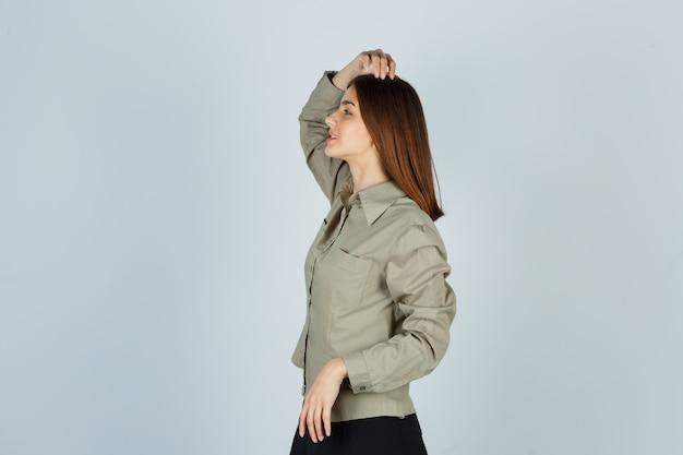 Портрет молодой женщины, держащей руку на голове в рубашке, юбке и выглядящей обнадеживающей