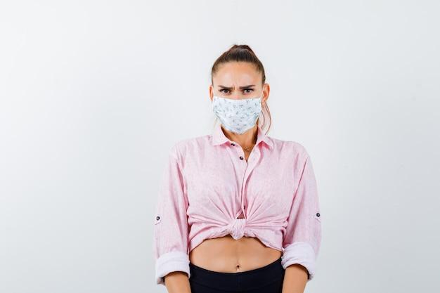 Портрет молодой женщины, смотрящей в камеру в рубашке, штанах, медицинской маске и серьезного вида спереди