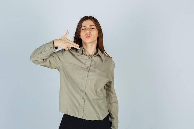 손가락 권총 기호를 만드는 젊은 여성의 초상화, 셔츠, 치마에 입술을 삐죽삐죽, 자신감 있는 전면 보기