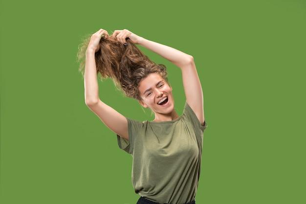 緑の壁に分離されたダンス若い女性モデルの肖像
