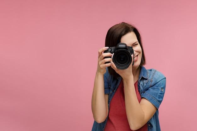 복사 공간와 분홍색 배경에 고립 된 젊은 여성 사진 작가의 초상화.