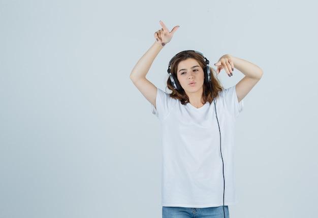 白いtシャツ、ジーンズ、夢のような正面図でヘッドフォンで音楽を楽しみながら離れて指している若い女性の肖像画
