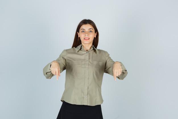 シャツ、スカート、陽気な正面図で下向きの若い女性の肖像画