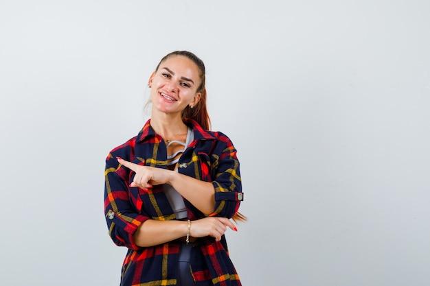 クロップトップ、市松模様のシャツ、パンツ、陽気な正面図で左側を指している若い女性の肖像画