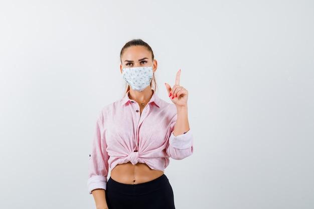 셔츠, 바지, 의료 마스크에서 가리키는 자신감 전면보기를 찾고 젊은 여성의 초상화