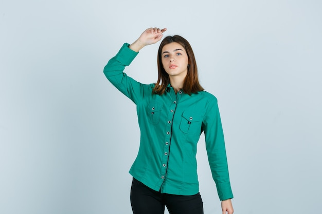 녹색 셔츠에 손을 들고 자신감 전면보기를 찾고있는 동안 포즈를 취하는 젊은 여성의 초상화