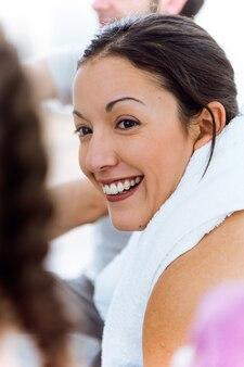 요가 매트에서 휴식을 취하고 운동 세션 후에 이야기하는 젊은 여성의 초상화.